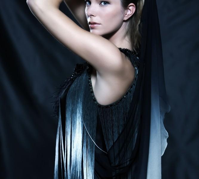 Woman wearing a fashionable white and black fringe dress.