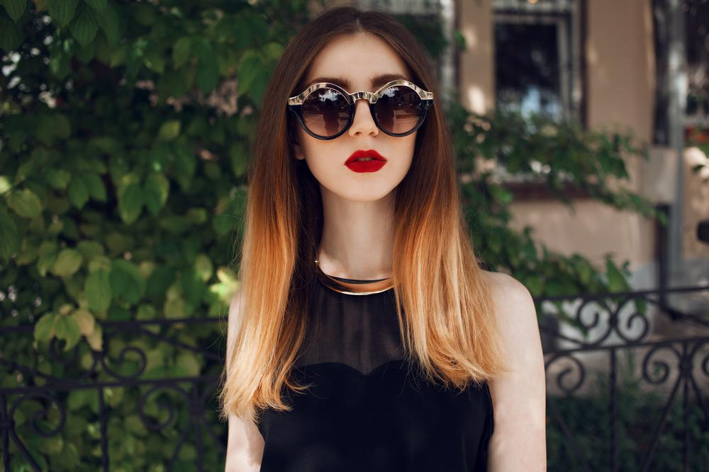 Stylish woman wearing sunglasses and showing off her ombre hair color.