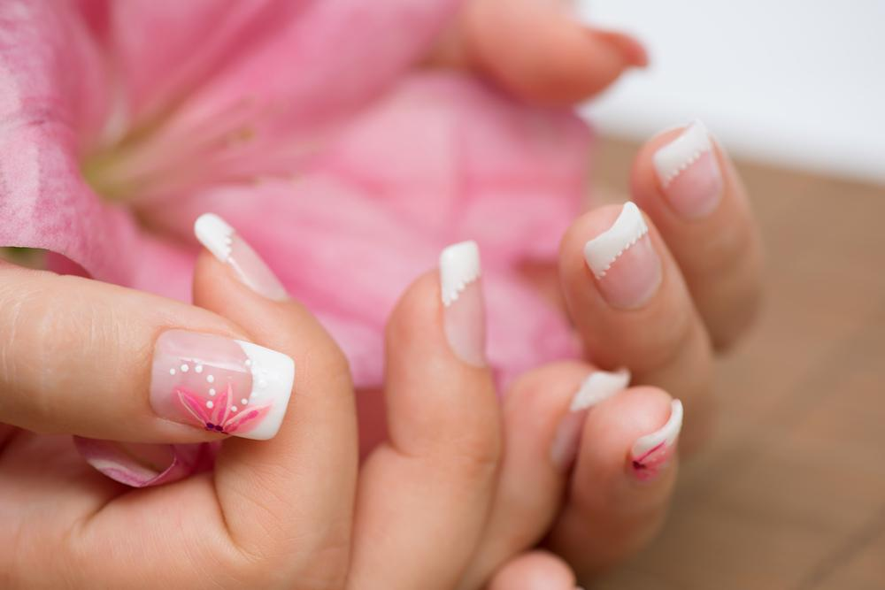 Woman with a french manicure and subdued pastel colors.