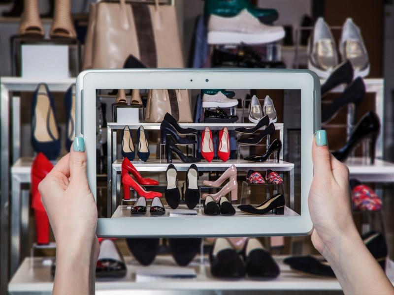 Woman taking a picture of sandals at a store with her tablet.