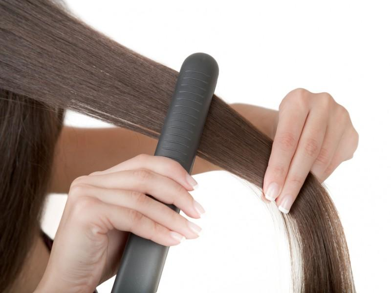 Woman straightening her hair.