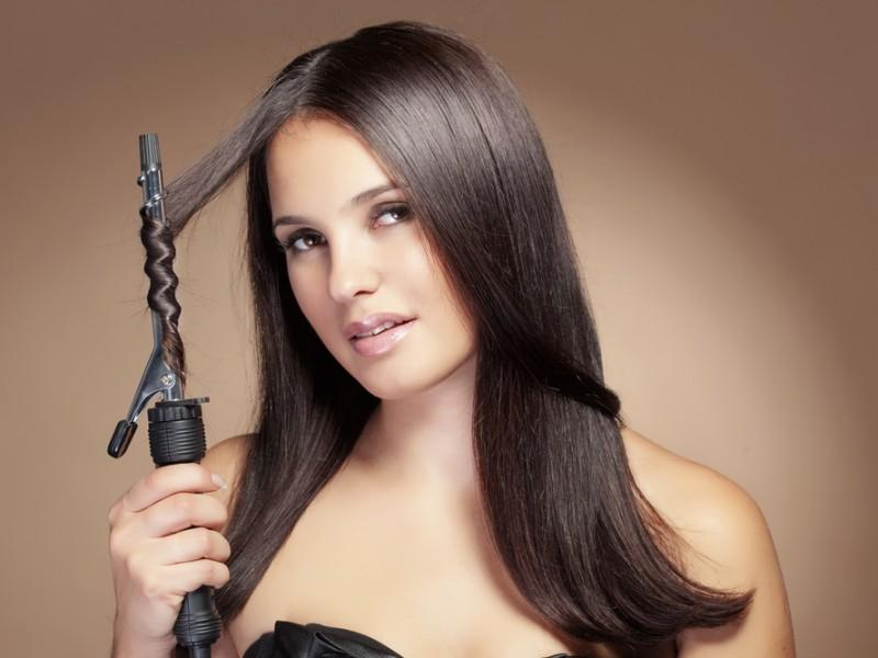 Woman using a curling iron on her hair.
