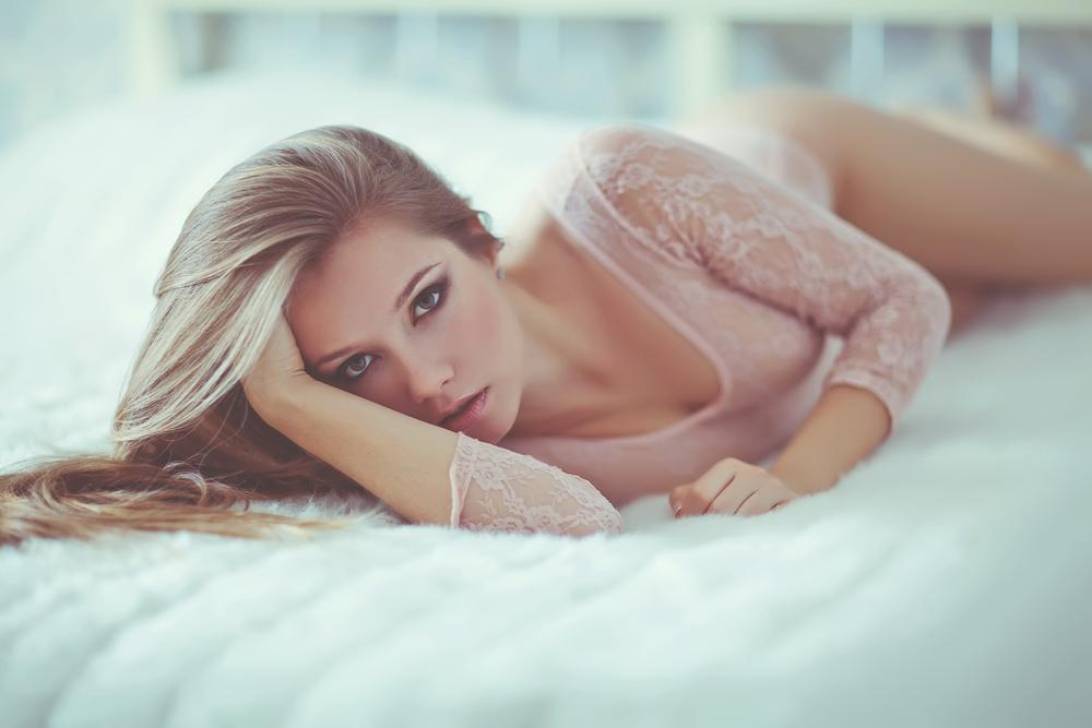 Woman in lingerie lying on her bed.