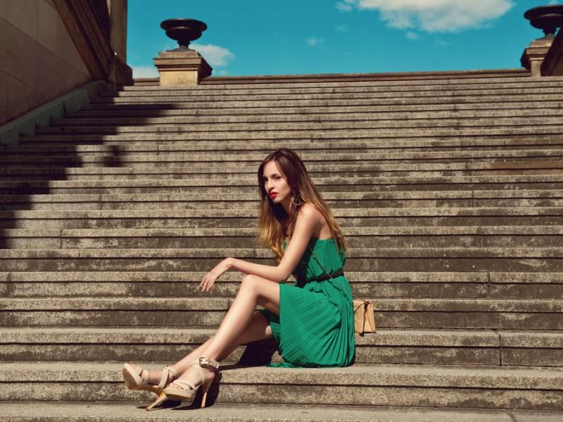 Woman wearing a stylish dress sitting on the stairs.