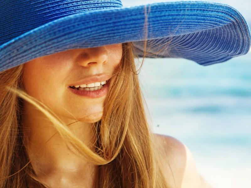 Woman wearing a hat in a beach.