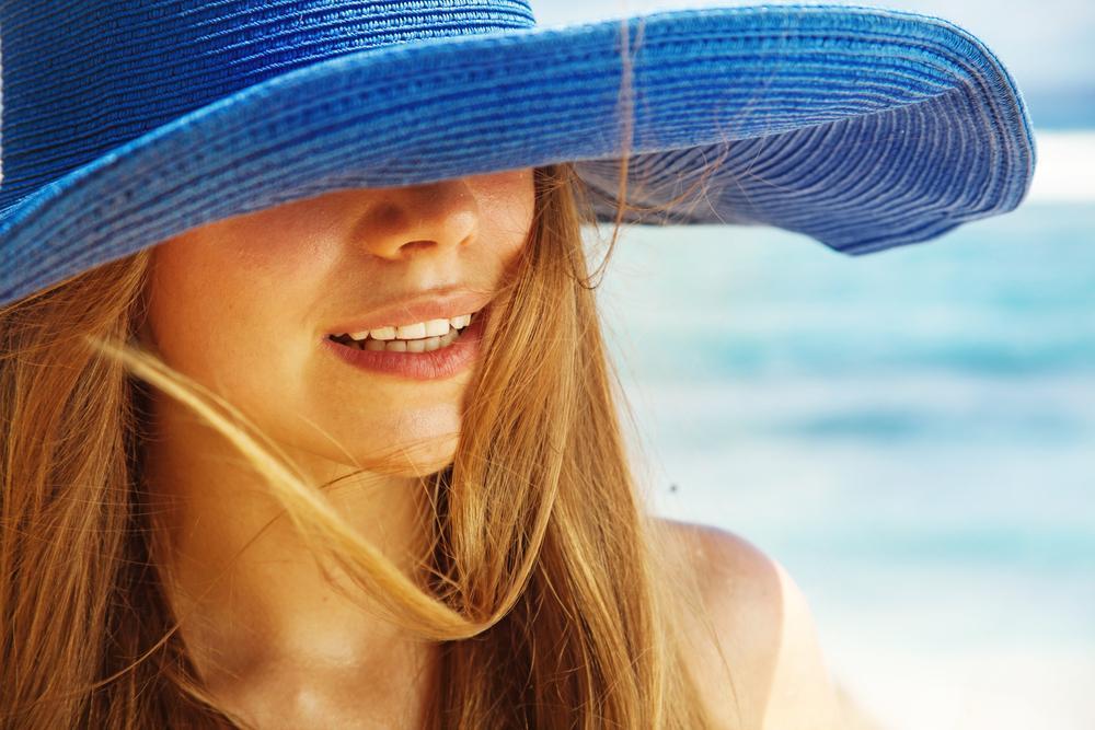 Woman wearing a hat in a beach.