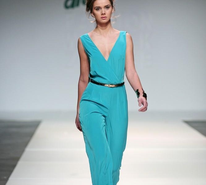 Model wearing overalls on the runway.