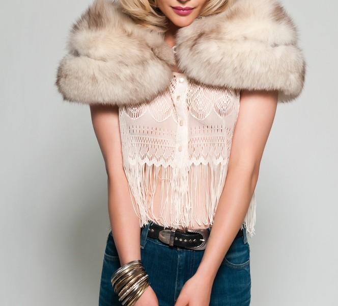 Woman wearing a fur stole and a fringe top.