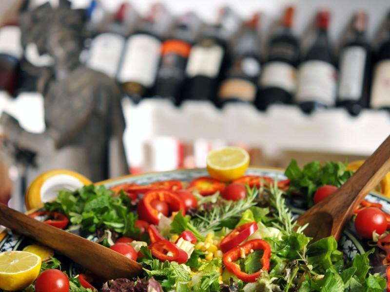 Closeup of a salad with wine bottles in the background
