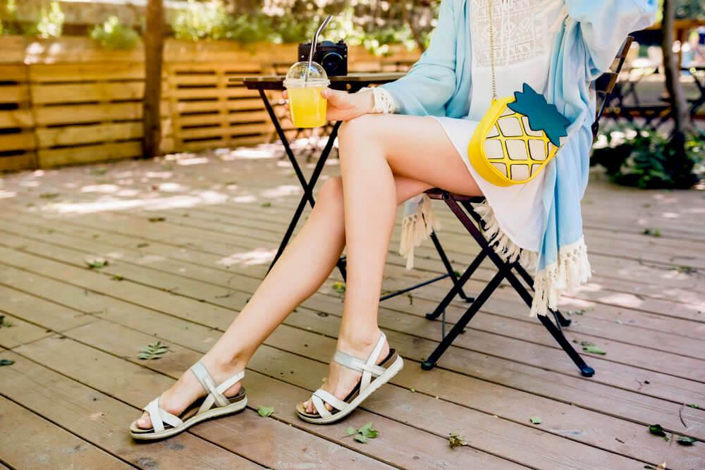 Woman's long legs in a pair of sandals outdoors