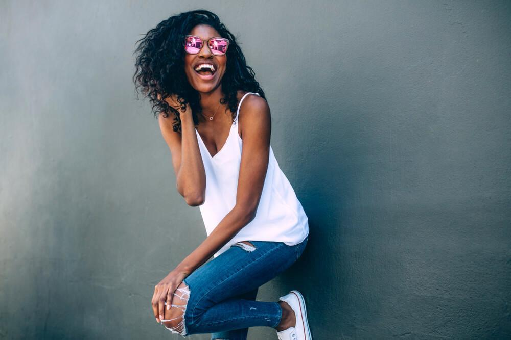 Laughing woman with pink sunglasses leaning against wall
