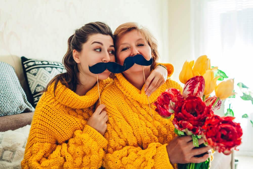 Mother and daughter with fake moustaches being silly and taking selfies