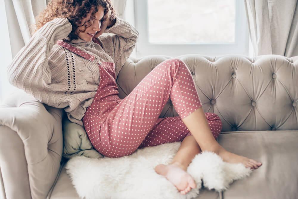 Woman wearing overalls over a jumper sitting on sofa