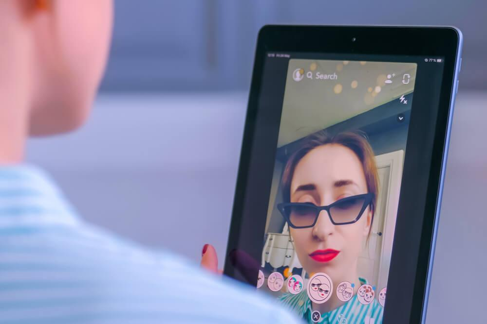 Woman taking selfie on Snapchat with filter