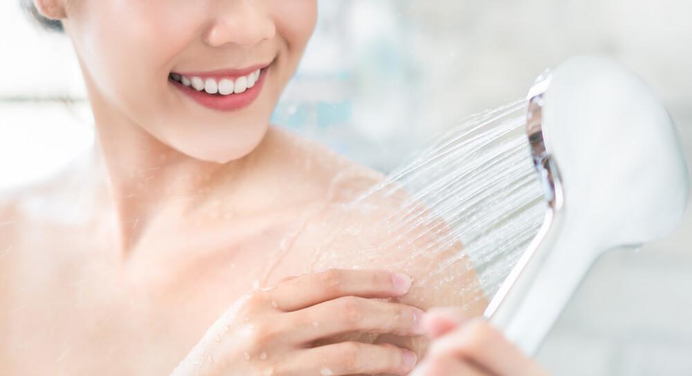 Woman showering her shoulder