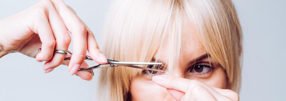 Woman cutting her own bangs