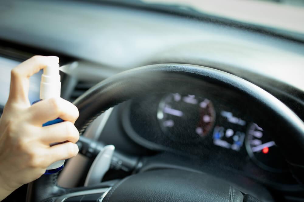 Hand spraying car steering wheel