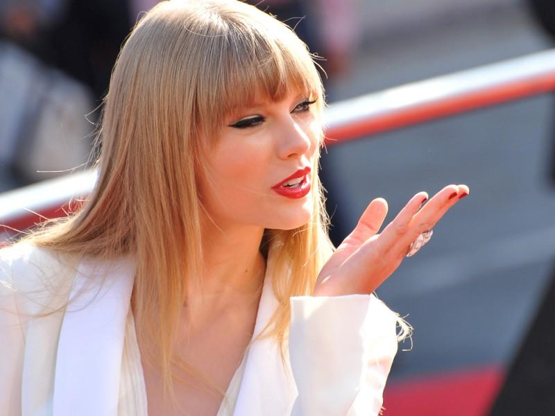 Taylor Swift blowing a flying kiss.
