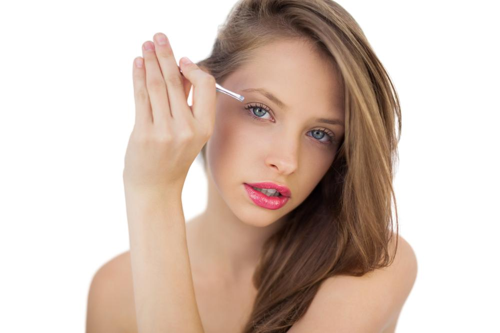 Woman plucking her eyebrows.