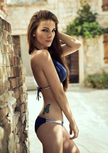 Woman wearing a bikini showing off her butterfly tattoo.