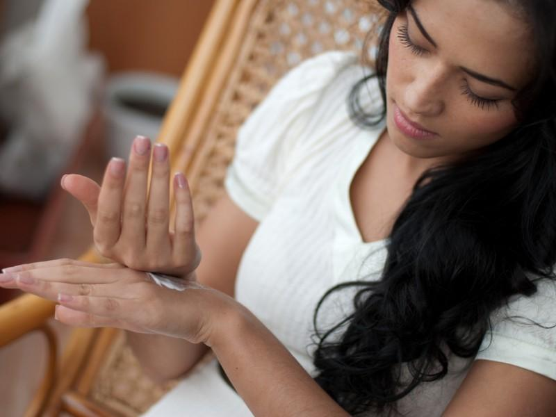 Woman applying lotion on her hands.