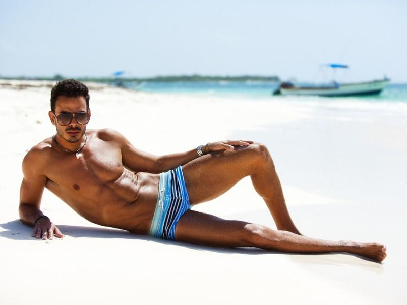 Stylish man wearing sunglasses in a beach.