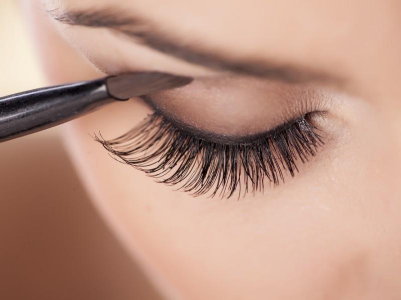 Woman applies smokey eye in brown shades