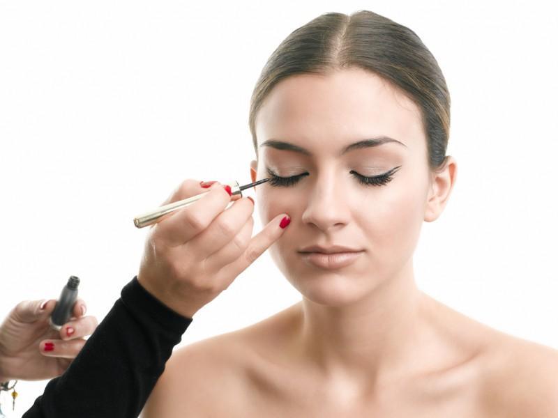 Stylist applying eye makeup.