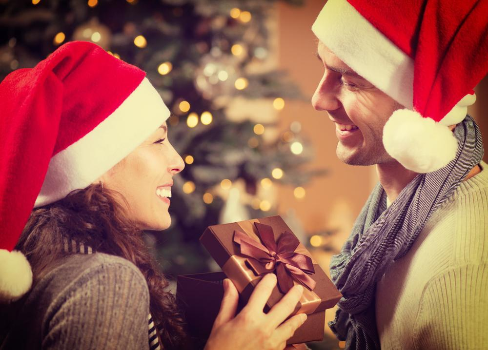 Wife giving a Christmas gift to her husband.
