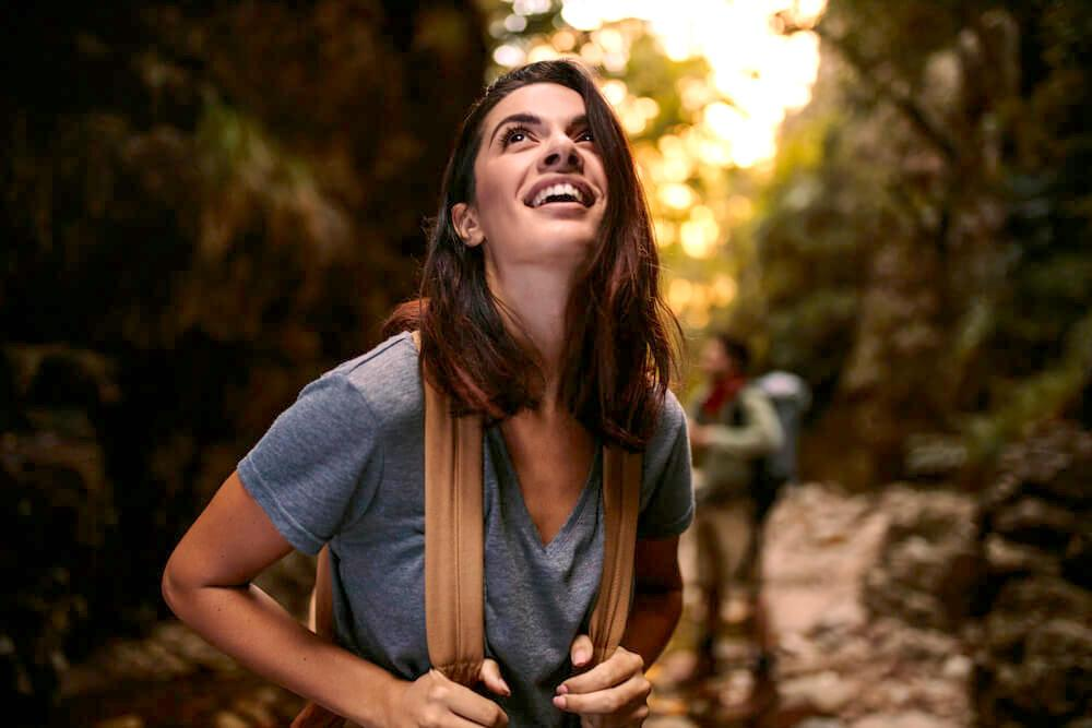 Smiling woman with backpack marvelling at her surroundings in nature