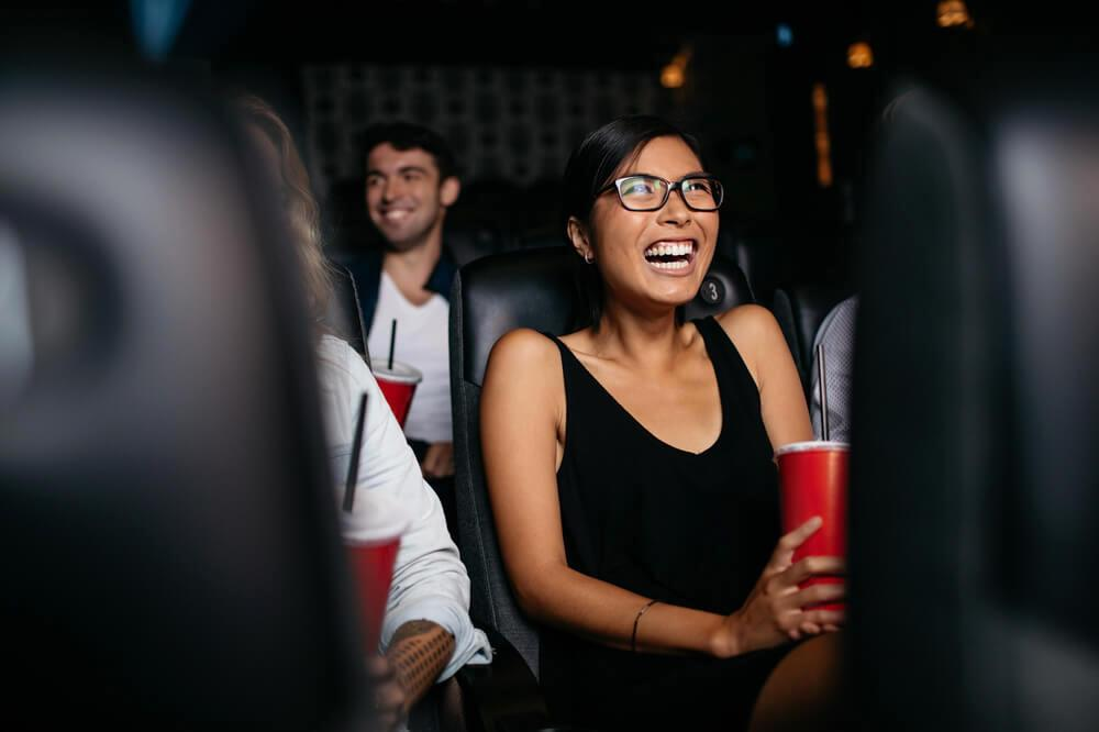 Woman laughing while watching movie in cinema