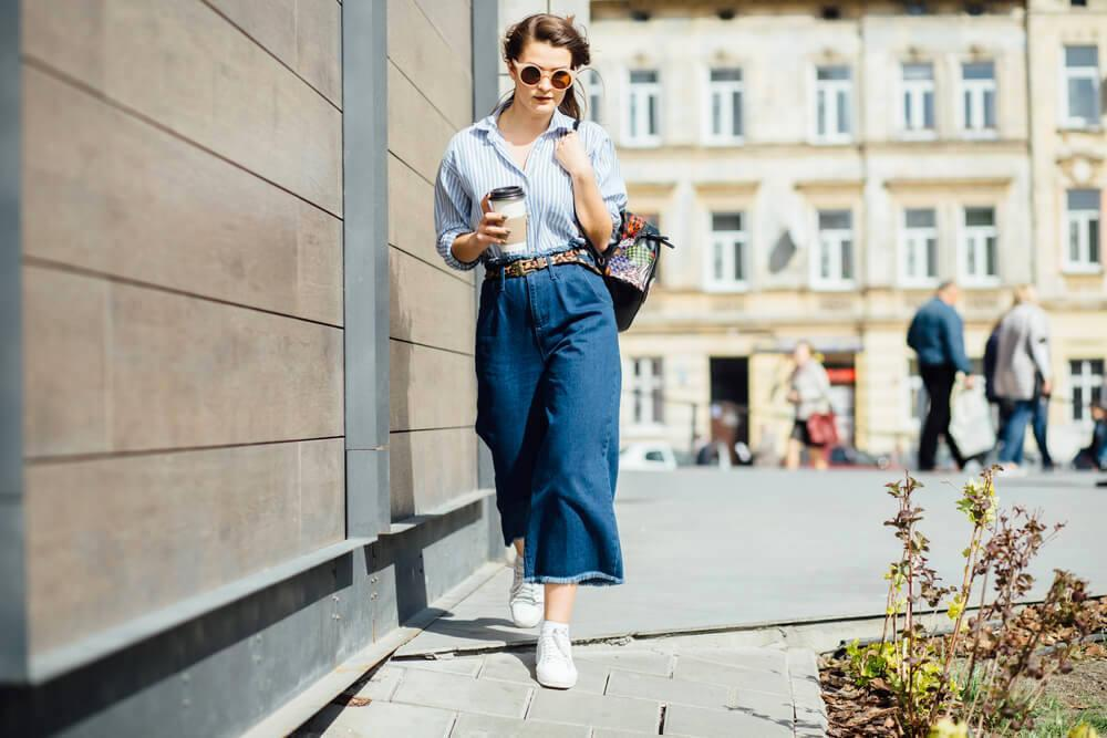 Stylish woman in denim walking in the street