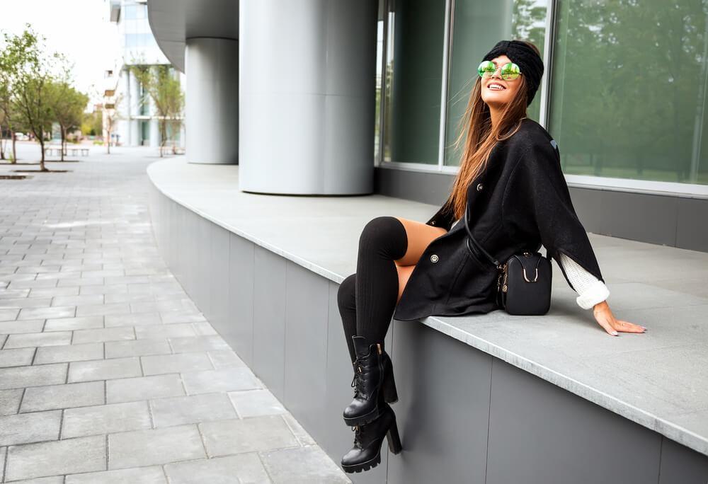 Stylish woman sitting by building